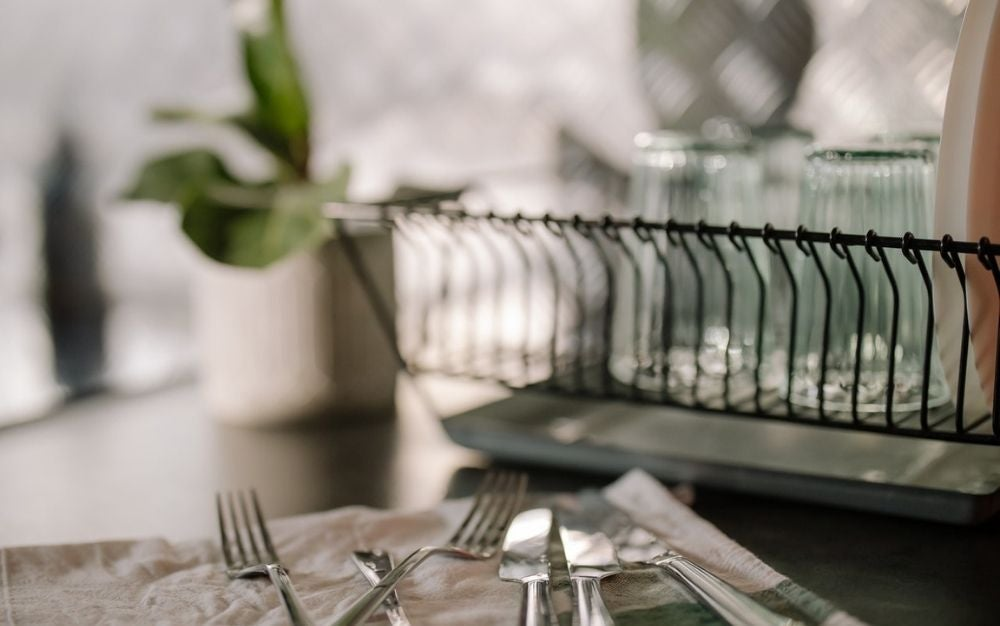 Some knives and forks placed on a white napkin near a dishwasher.