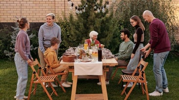 A large family who is eating out sitting on some new wooden furniture outside.