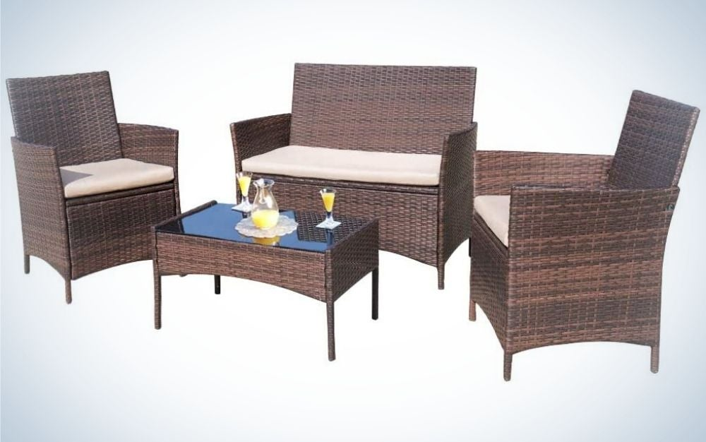 Some outdoor furniture with two single chairs and a beige and brown double chair and a wooden table in the middle.