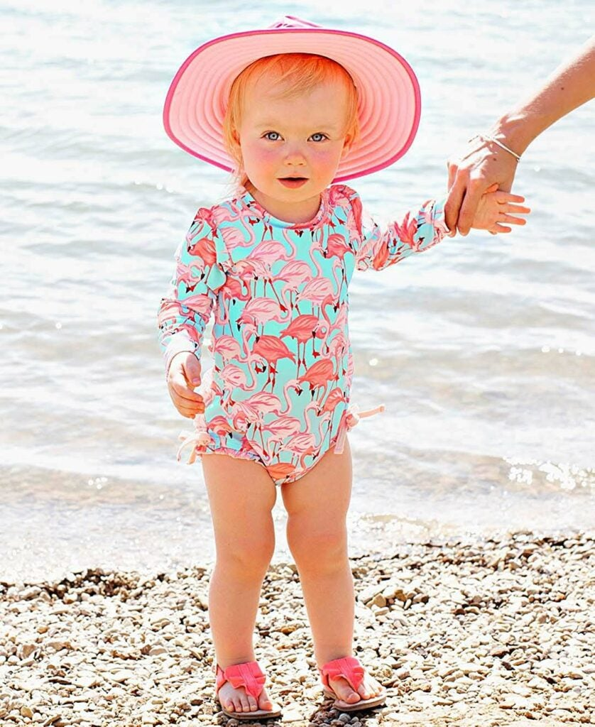 Little girl on the beach wearing a hat and flamingo bathingsuit