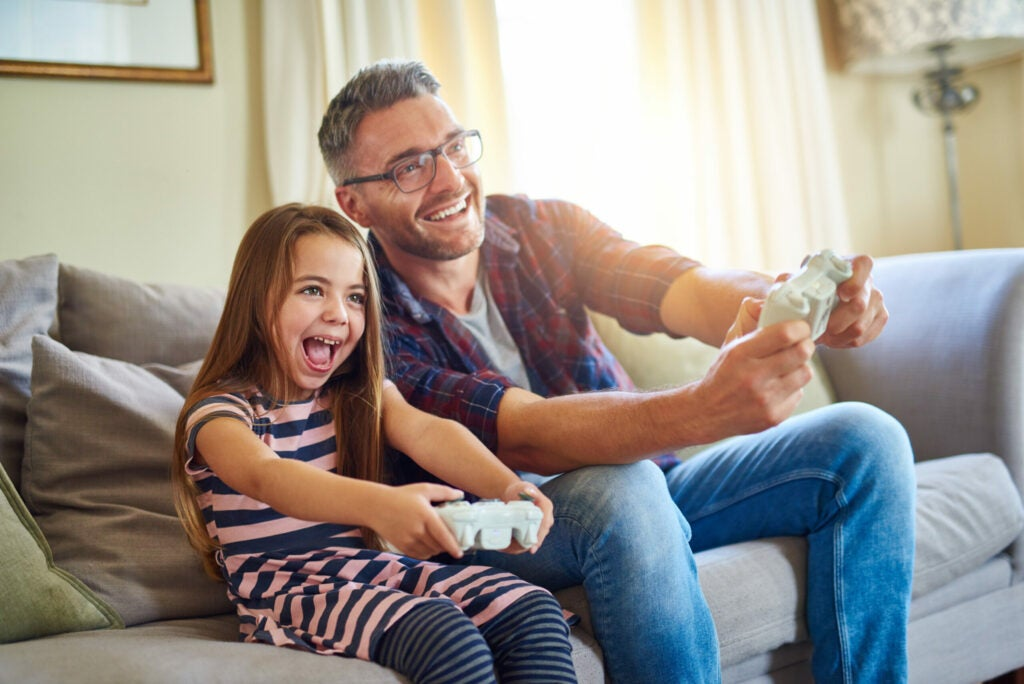 Shot of a father and daughter playing video games