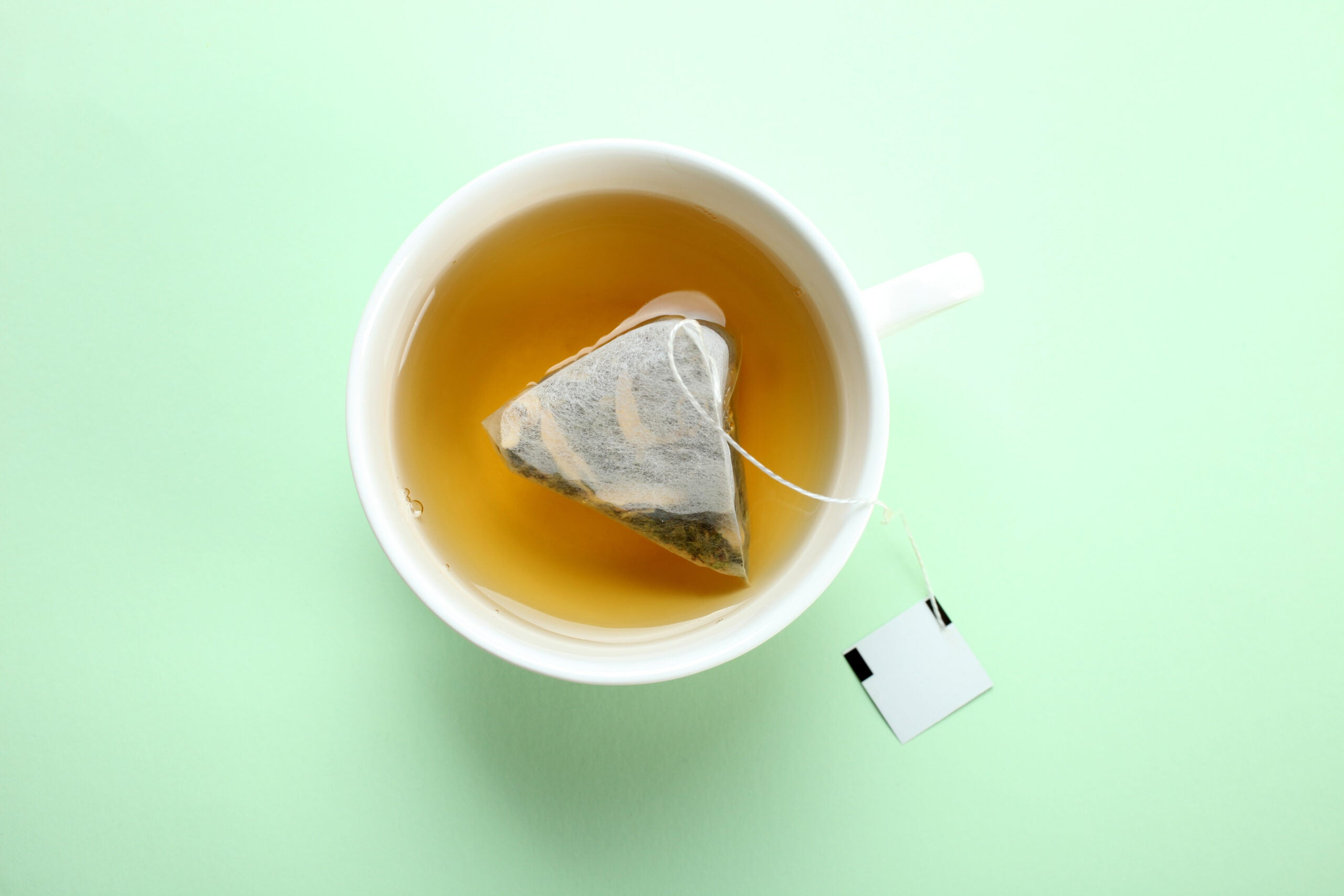 Mint tea bag in a cup on a mint pastel background. Top view.