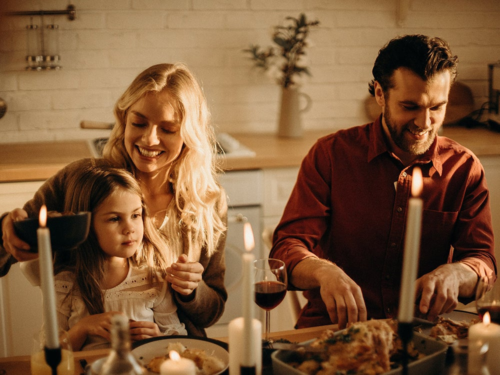 Family having dinner by candlelight