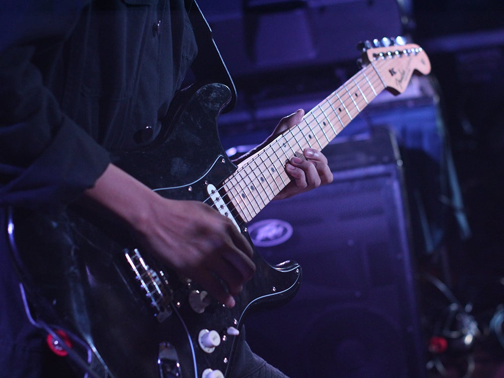 Person playing black stratocaster guitar