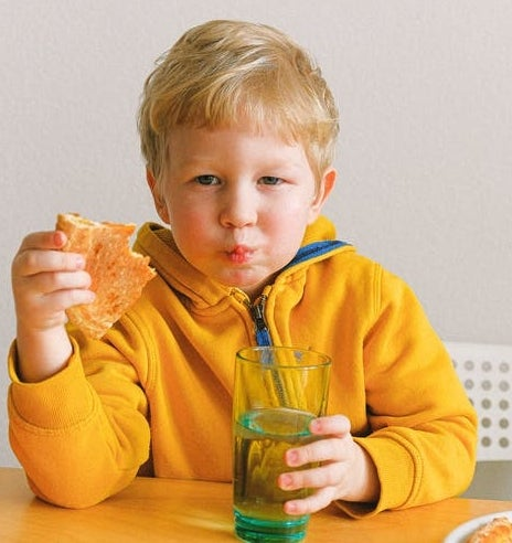 young boy eating at table top