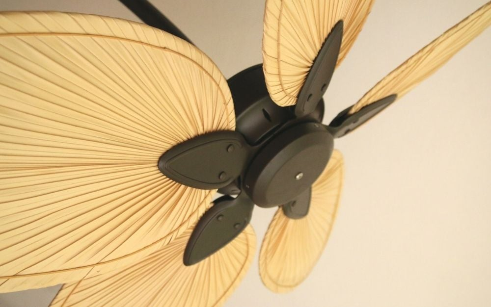 A ceiling fan with four wooden wings and in the center a black metal that is its engine.