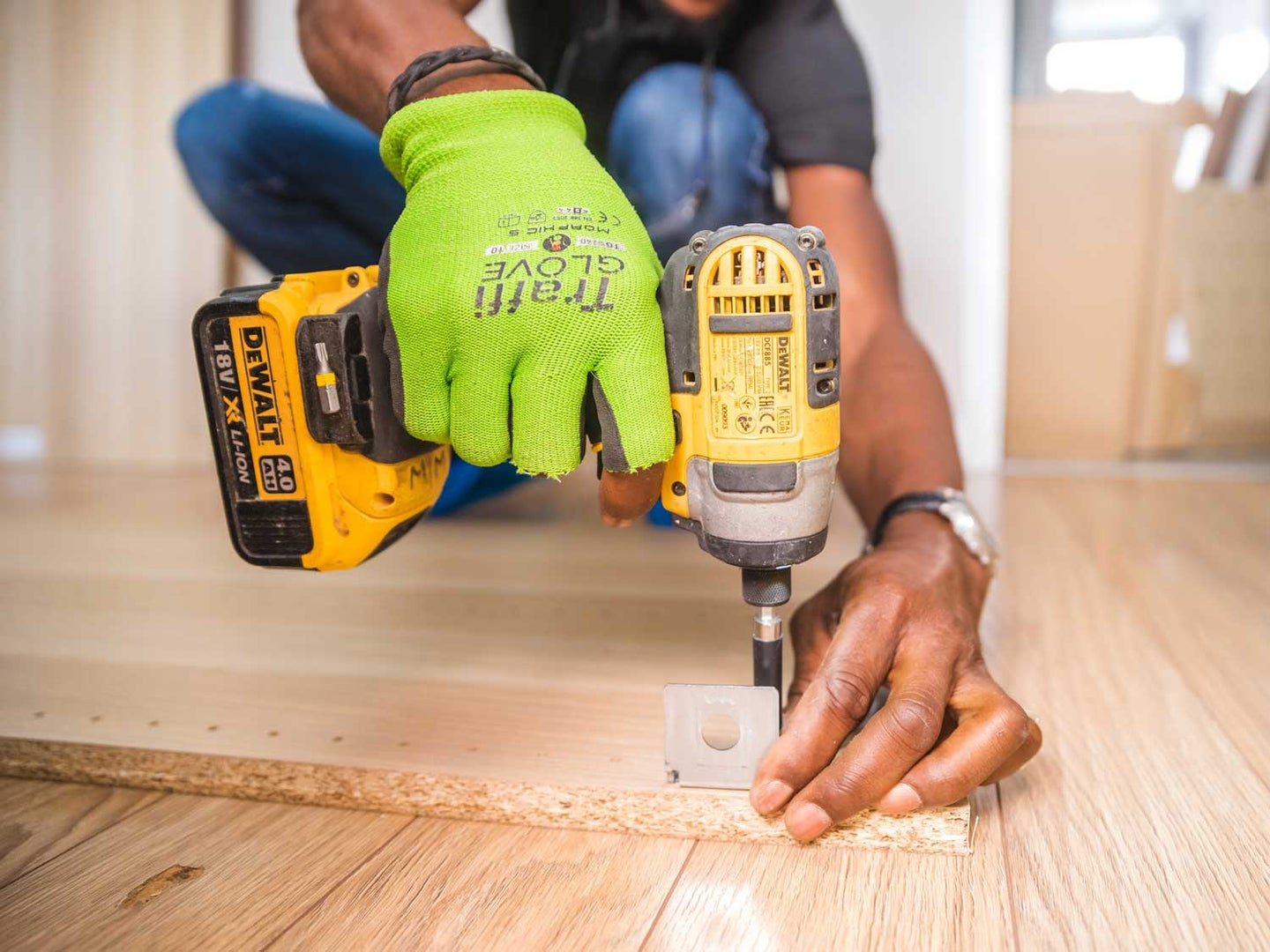 Person using Dewalt cordless impact driver on brown board.