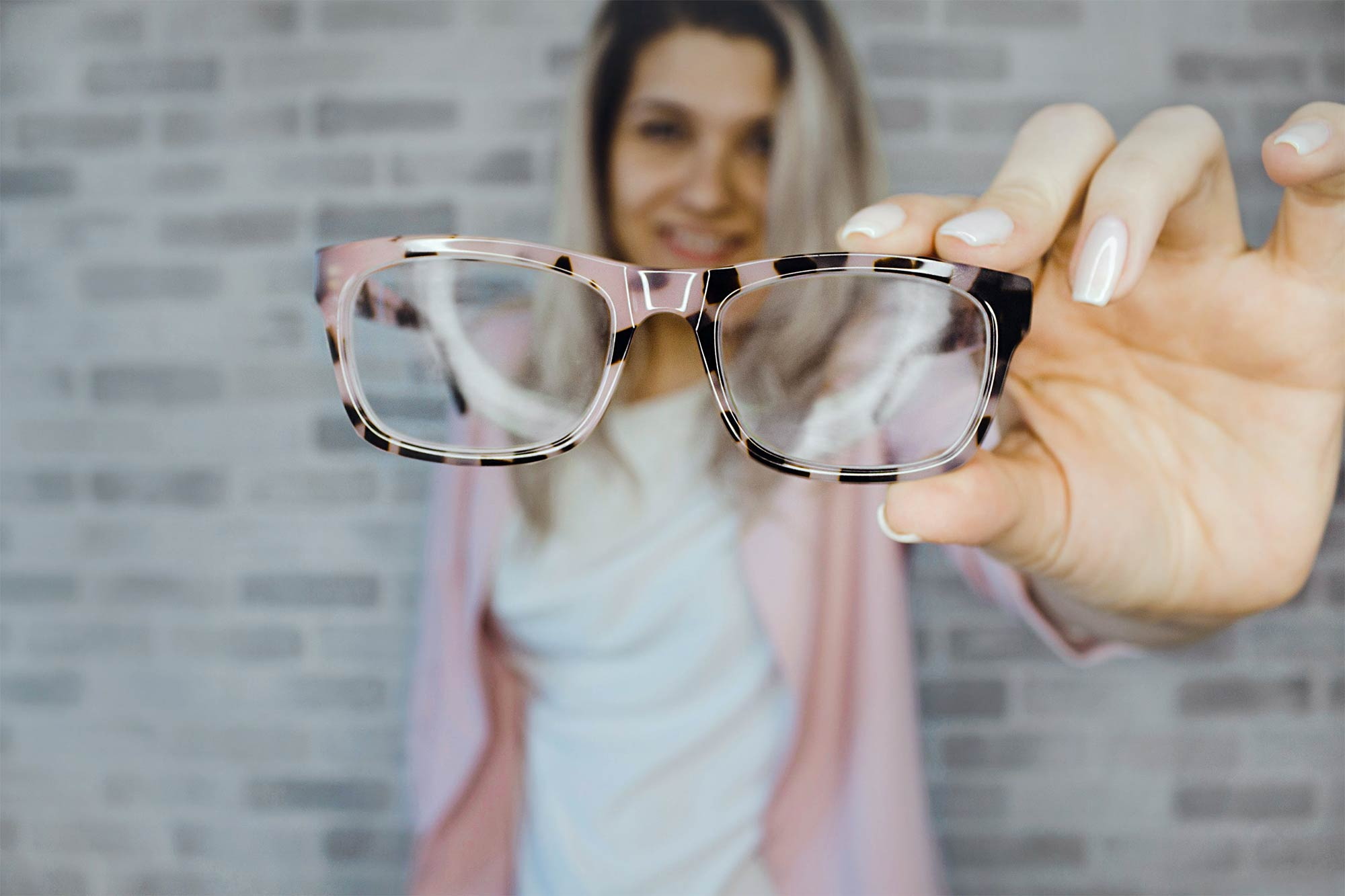 Woman holding up a pair of reading glasses