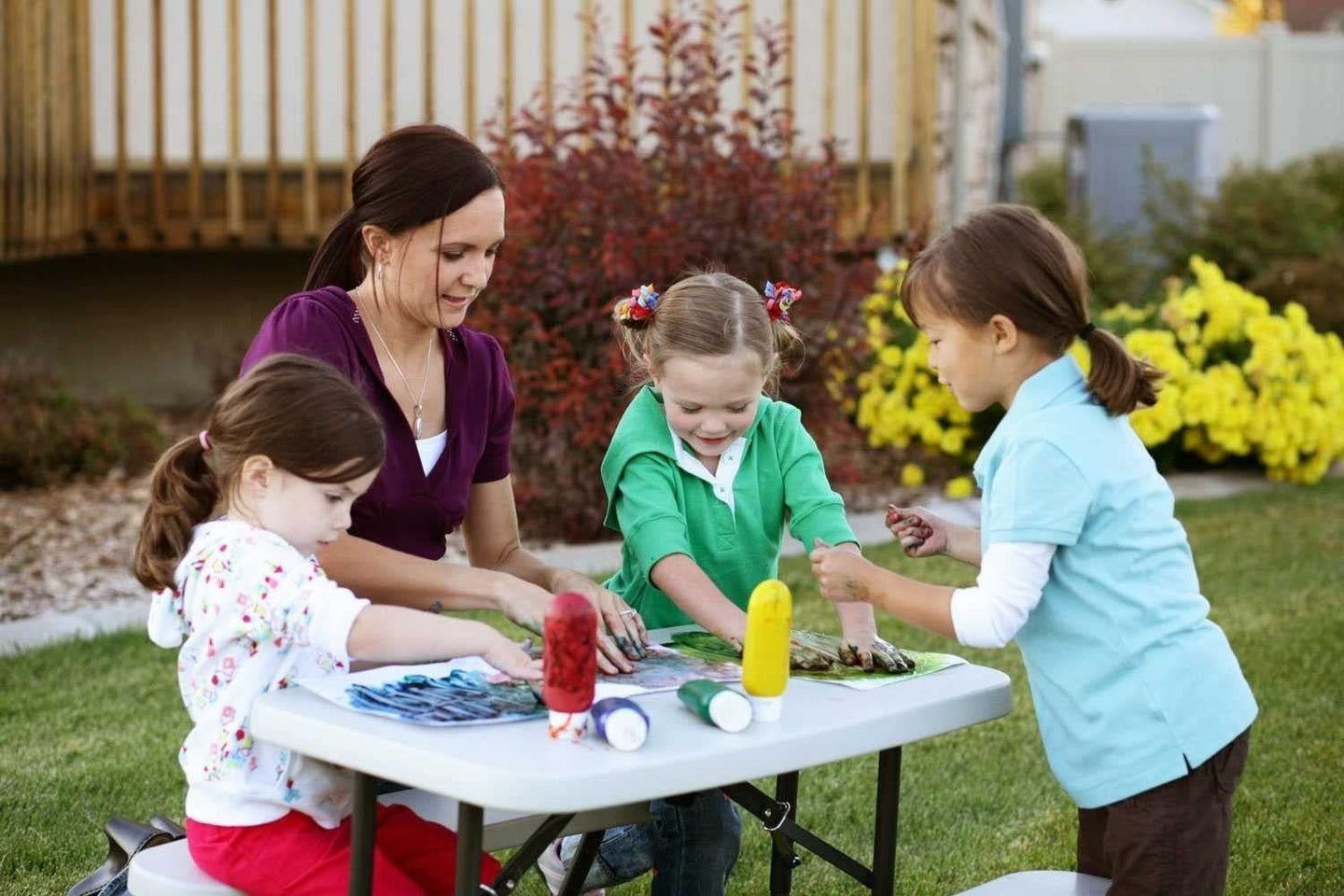 3 Children playing on a picnic table.