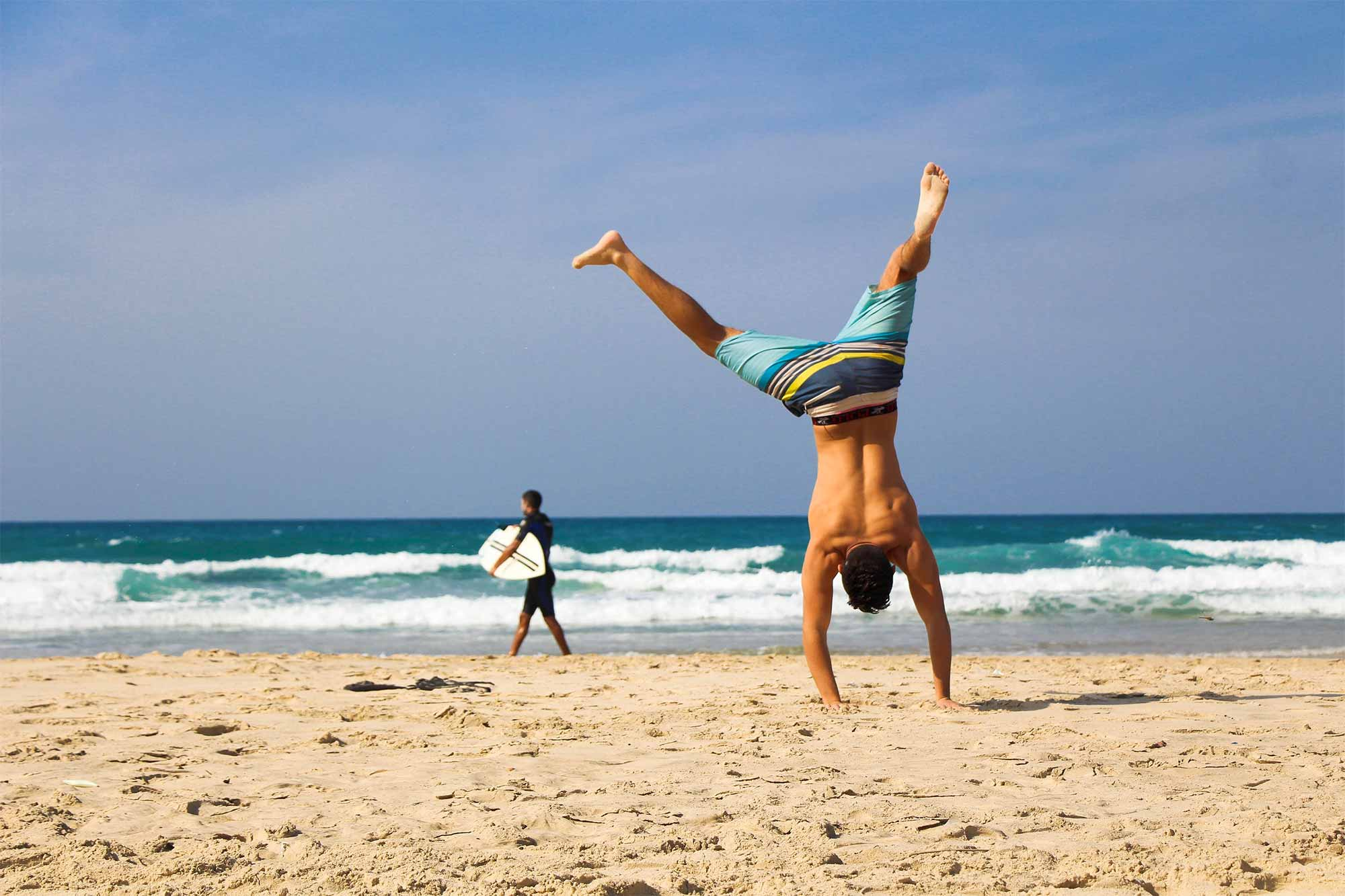 Man doing cartwheels on the beach