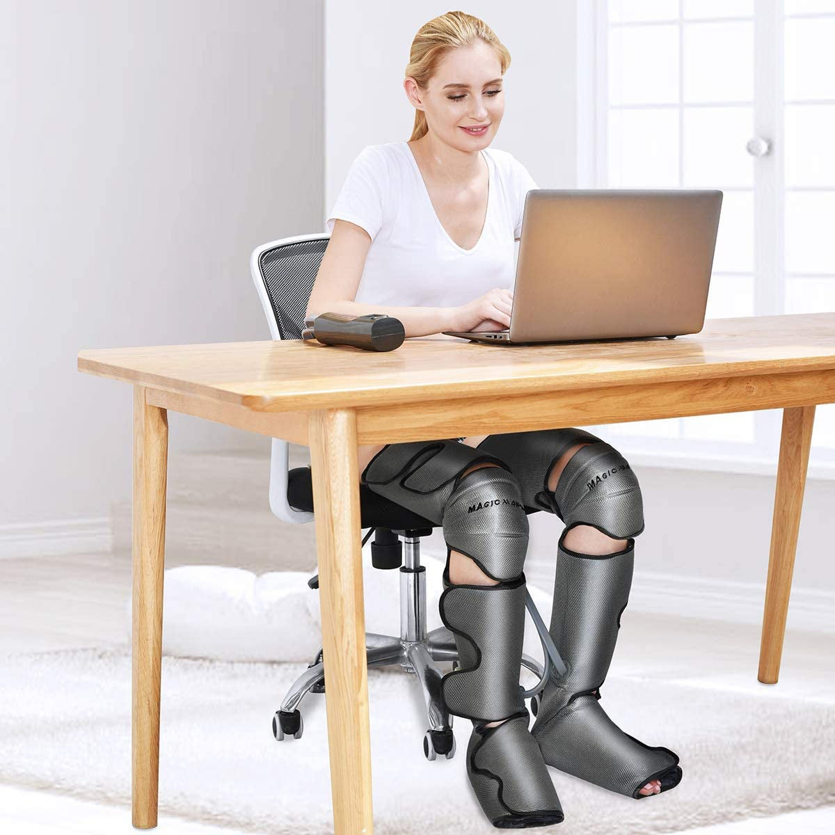 Woman sitting at desk with giant leg massagers on