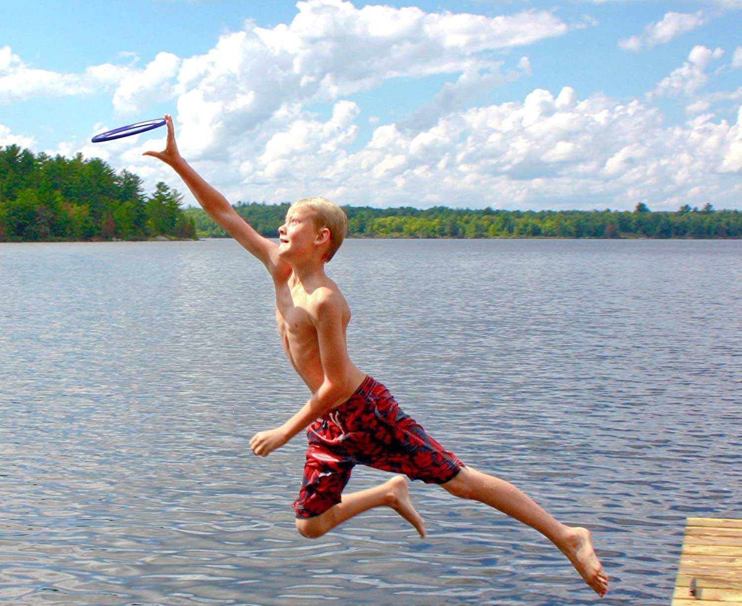 Boy playing with flying disc in the water