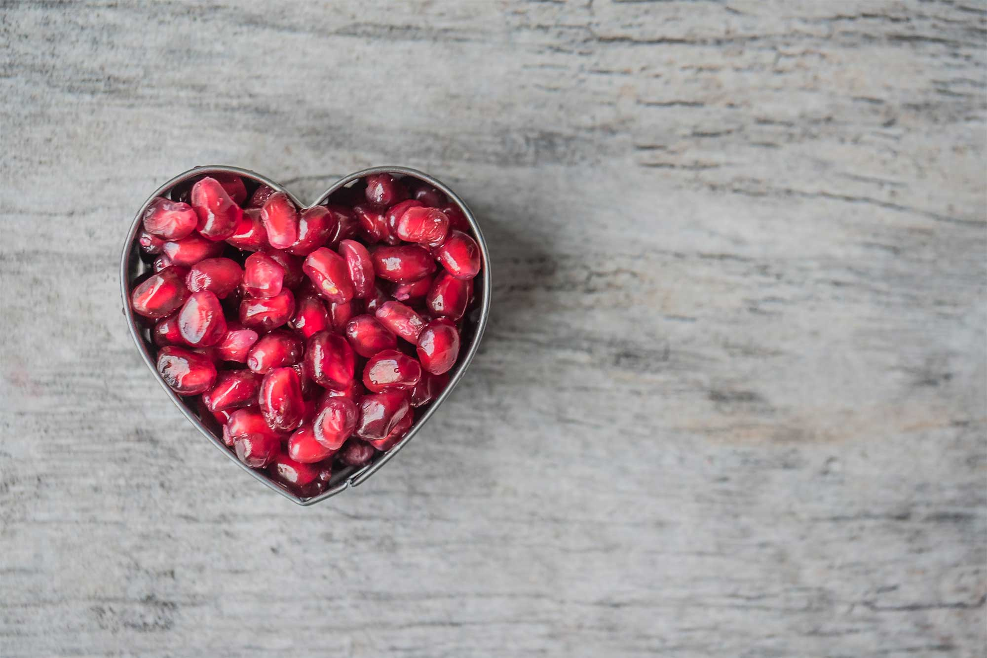 Pomegranate seeds arranged in a heart shape