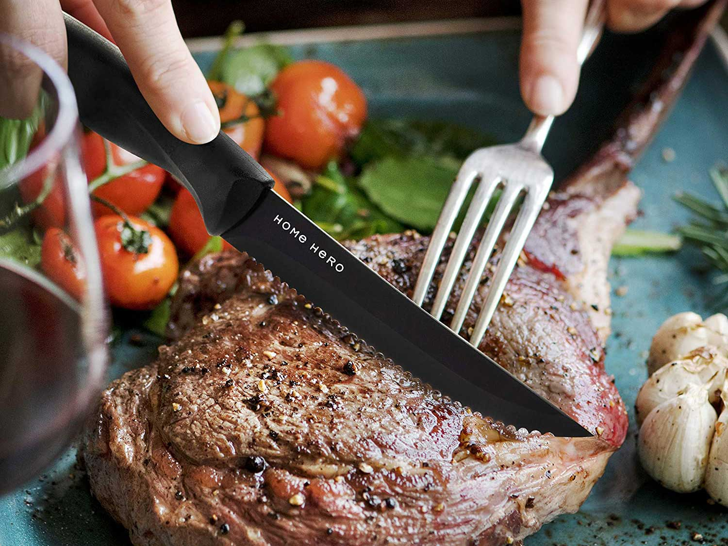 Person cuts steak with serrated steak knife