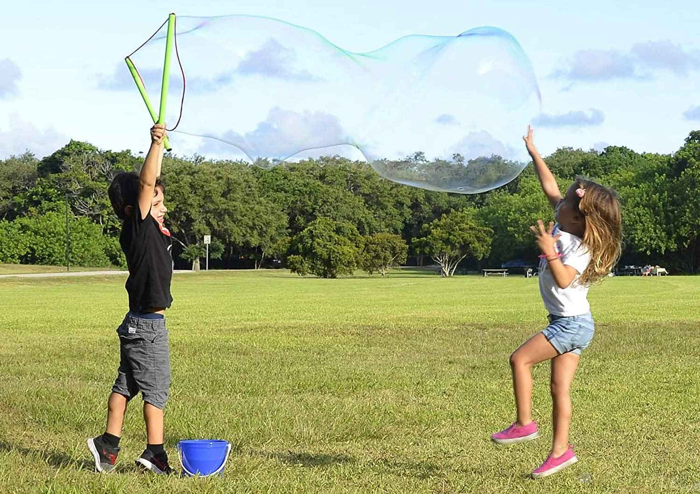 Two kids playing with giant bubbles in a park
