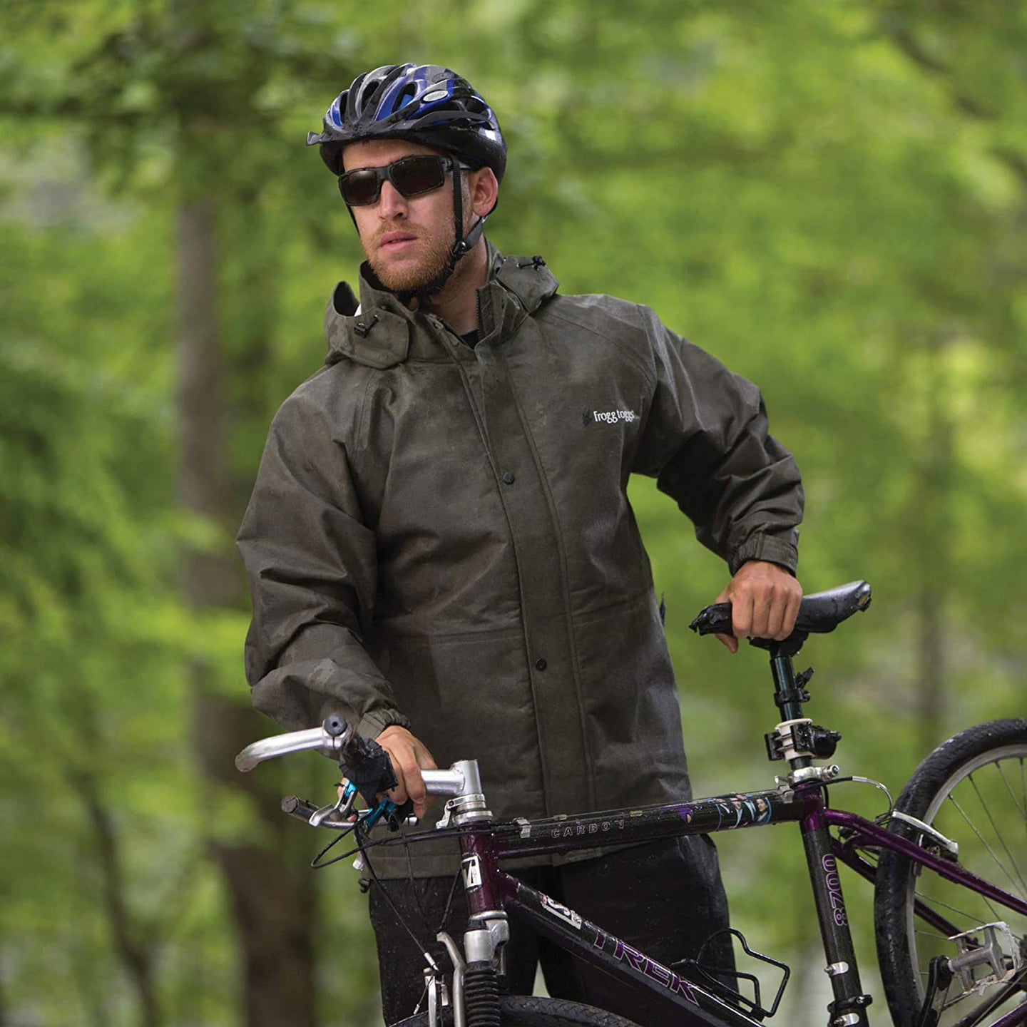 Guy in a helmet and sunglasses holding a bicycle