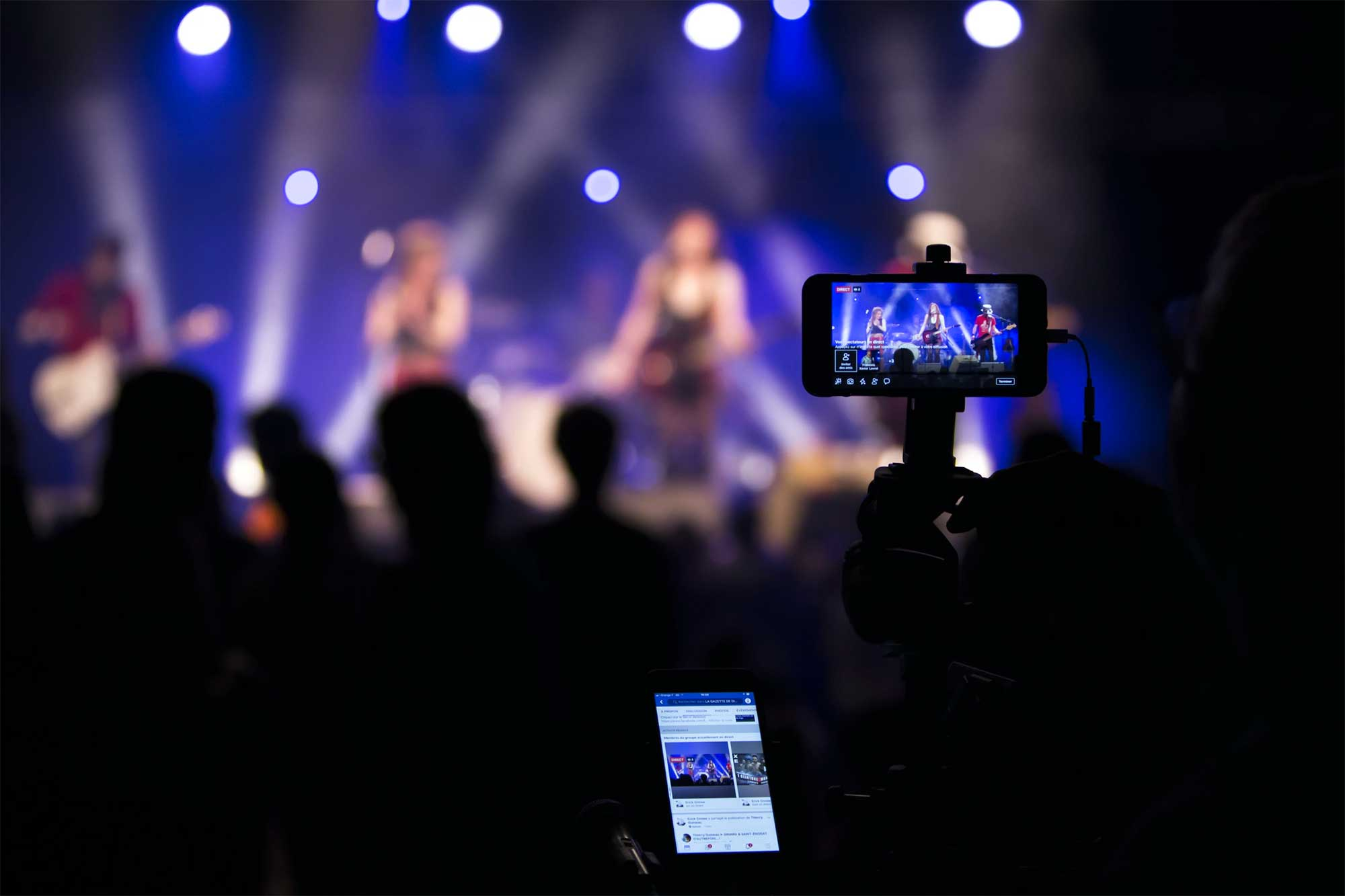 Person recording a concert in the crowd