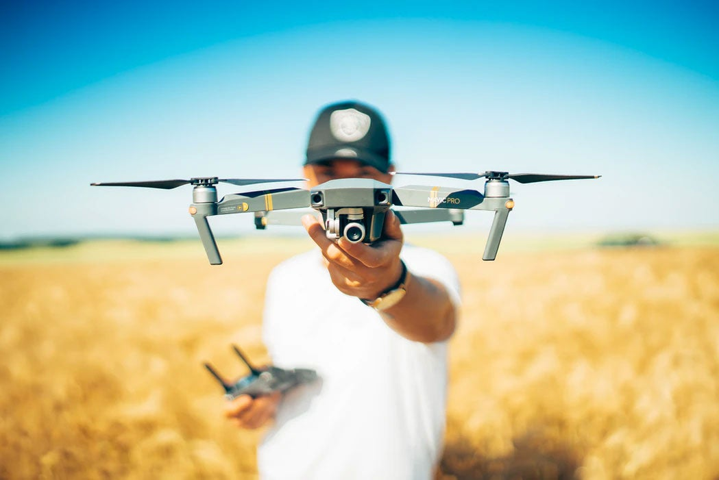 Guy in a field holding a quadcopter