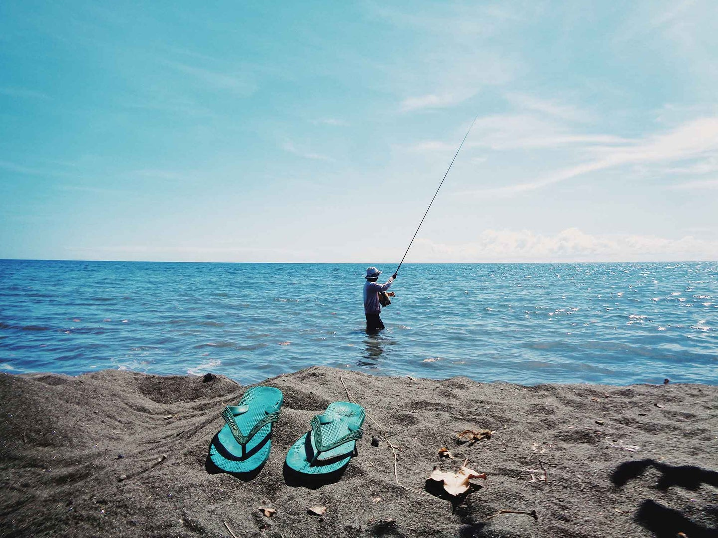 Guy fishing in the ocean with sandals on the beach