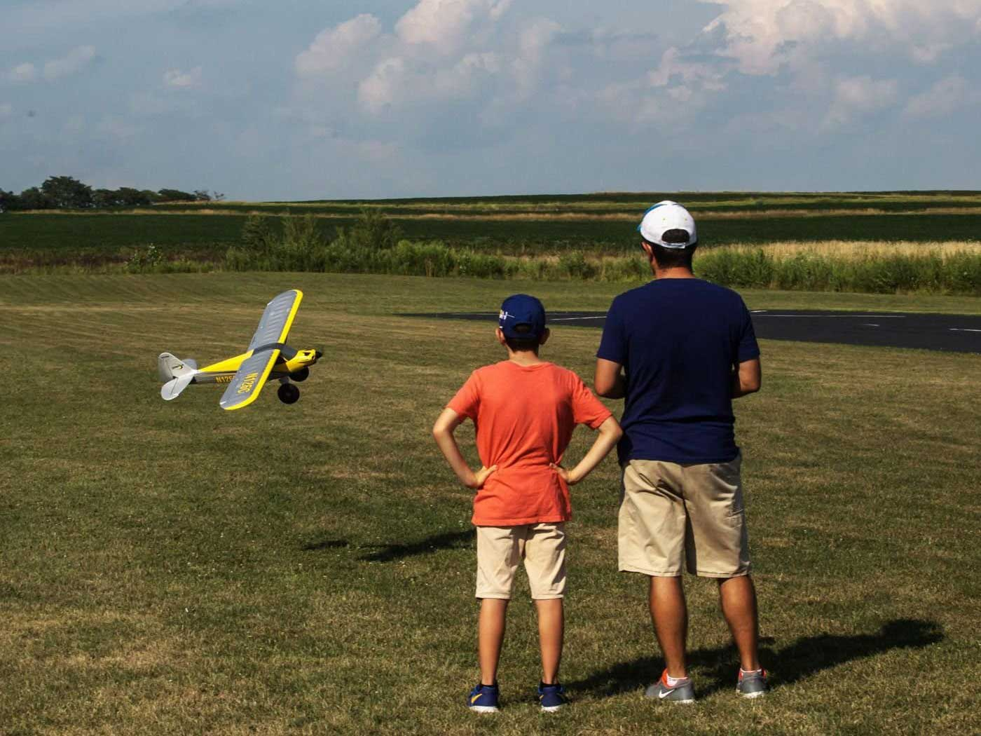 Father and son fly remote-controlled airplane