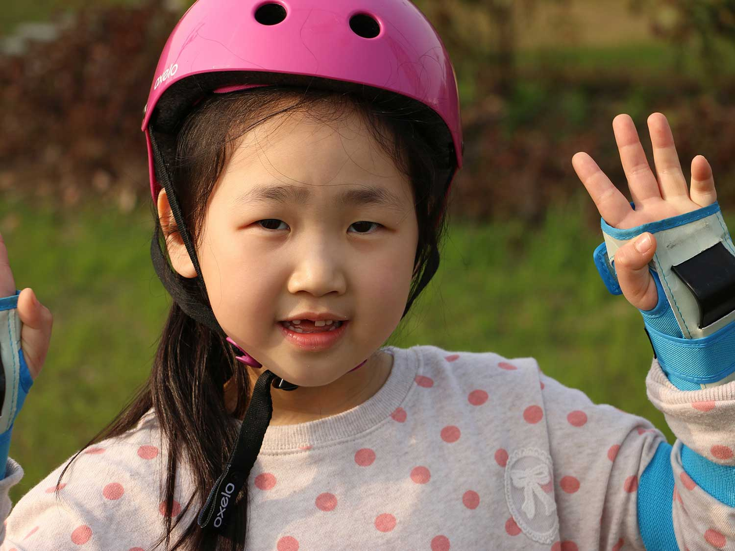 Girl with pads and helmet for roller skating