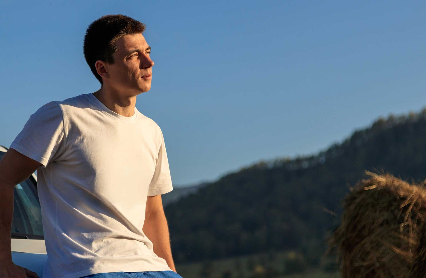 Guy in a white tee shirt gazing out