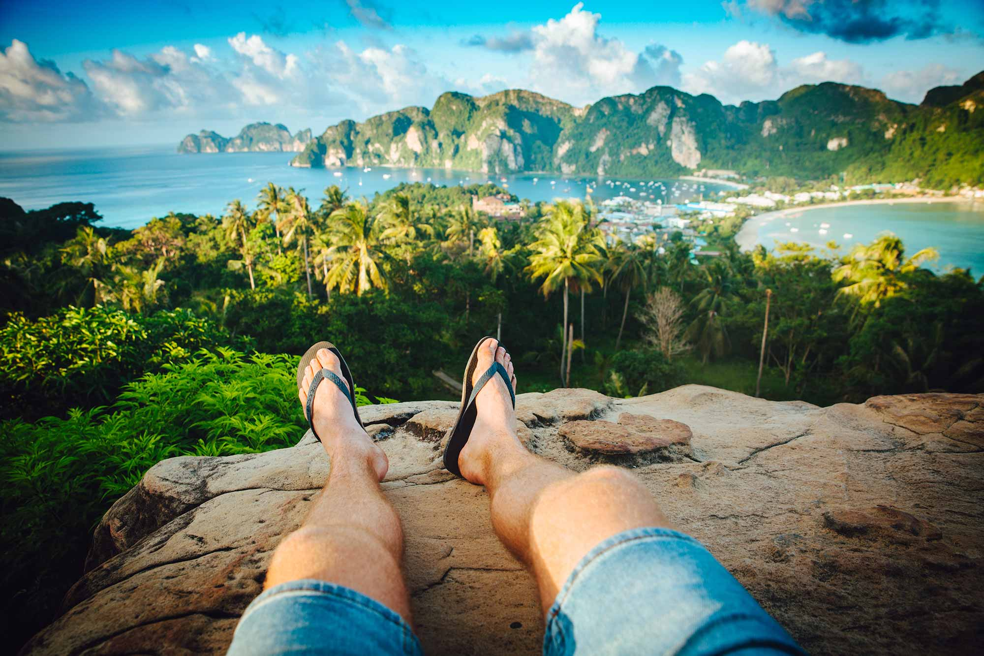 Person sitting on cliff overlooking a beautiful island.