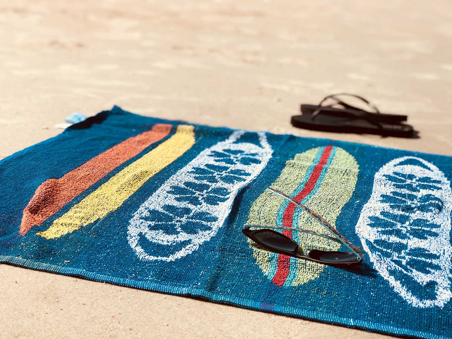 Towel on beach with flip-flop sandals and sunglasses.