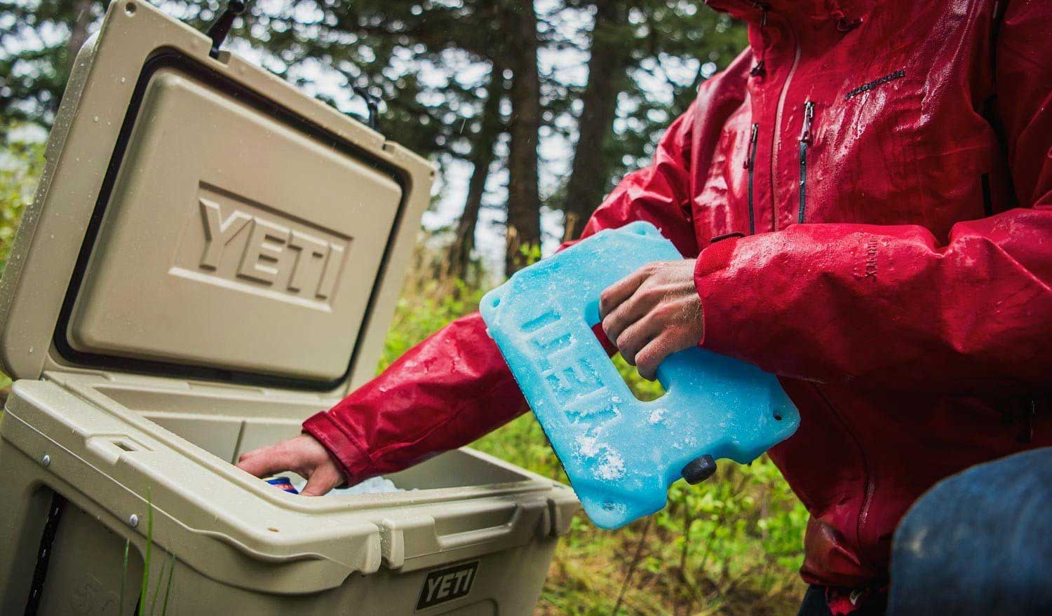 Person putting a Yeti ice pack into a cooler