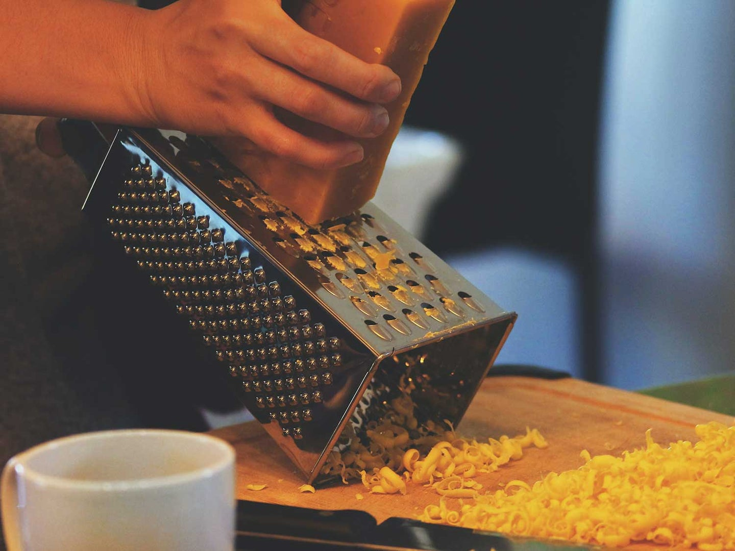 Grating block of cheese with cheese grater.
