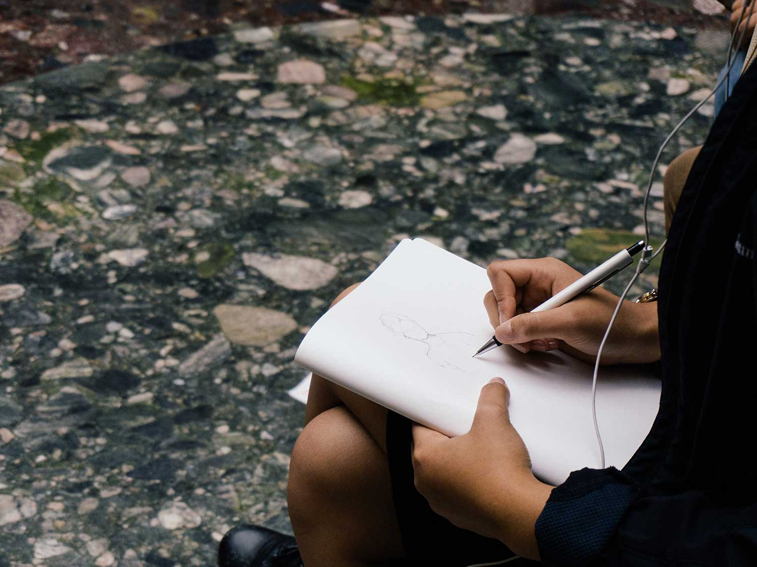 Woman drawing on sketch pad.