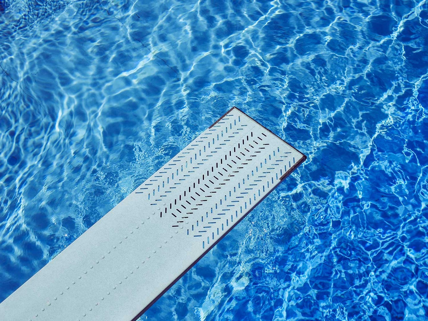 Diving board on top of pool with blue water.