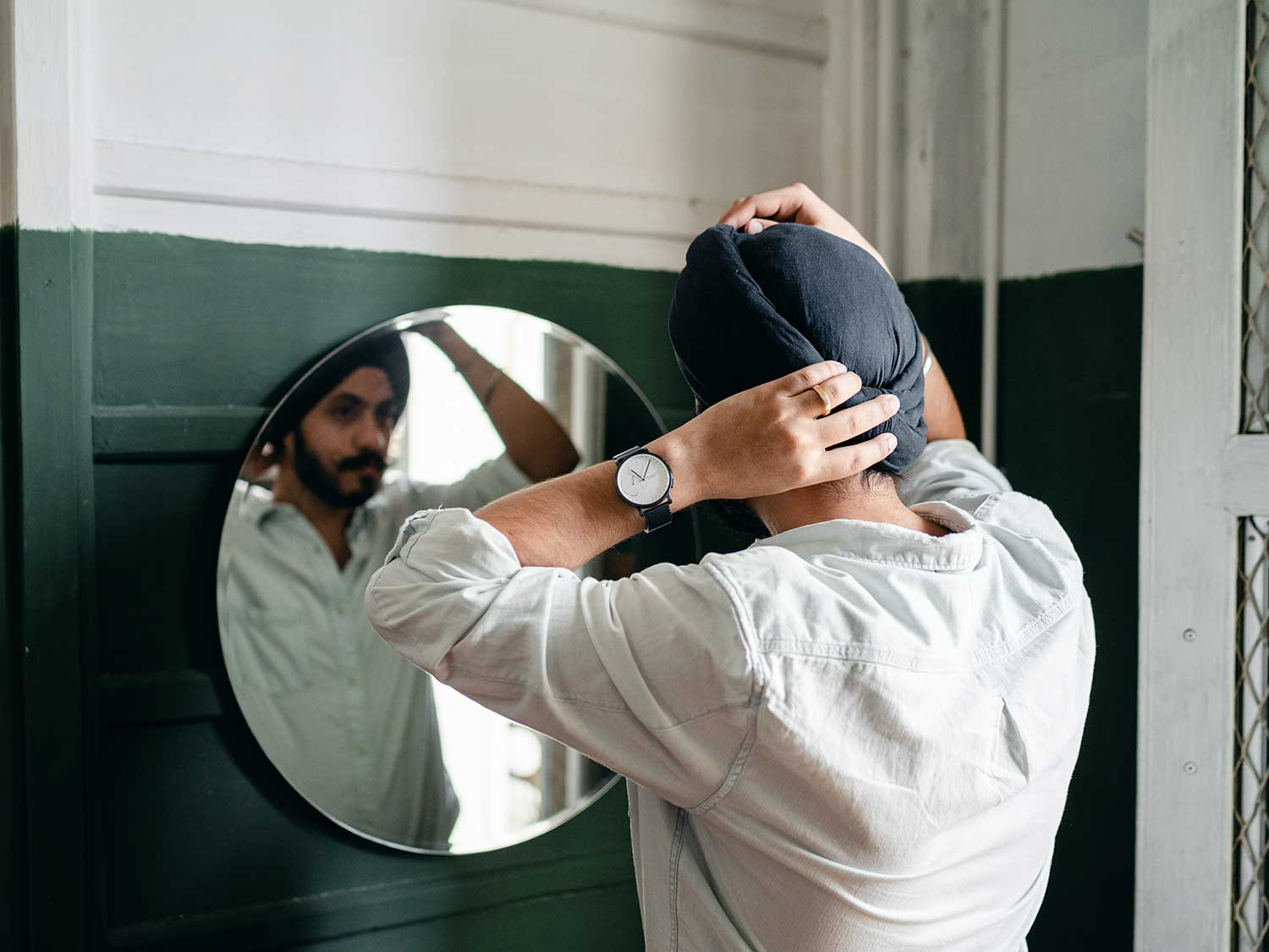Man adjusting turban in mirror with watch on left hand.