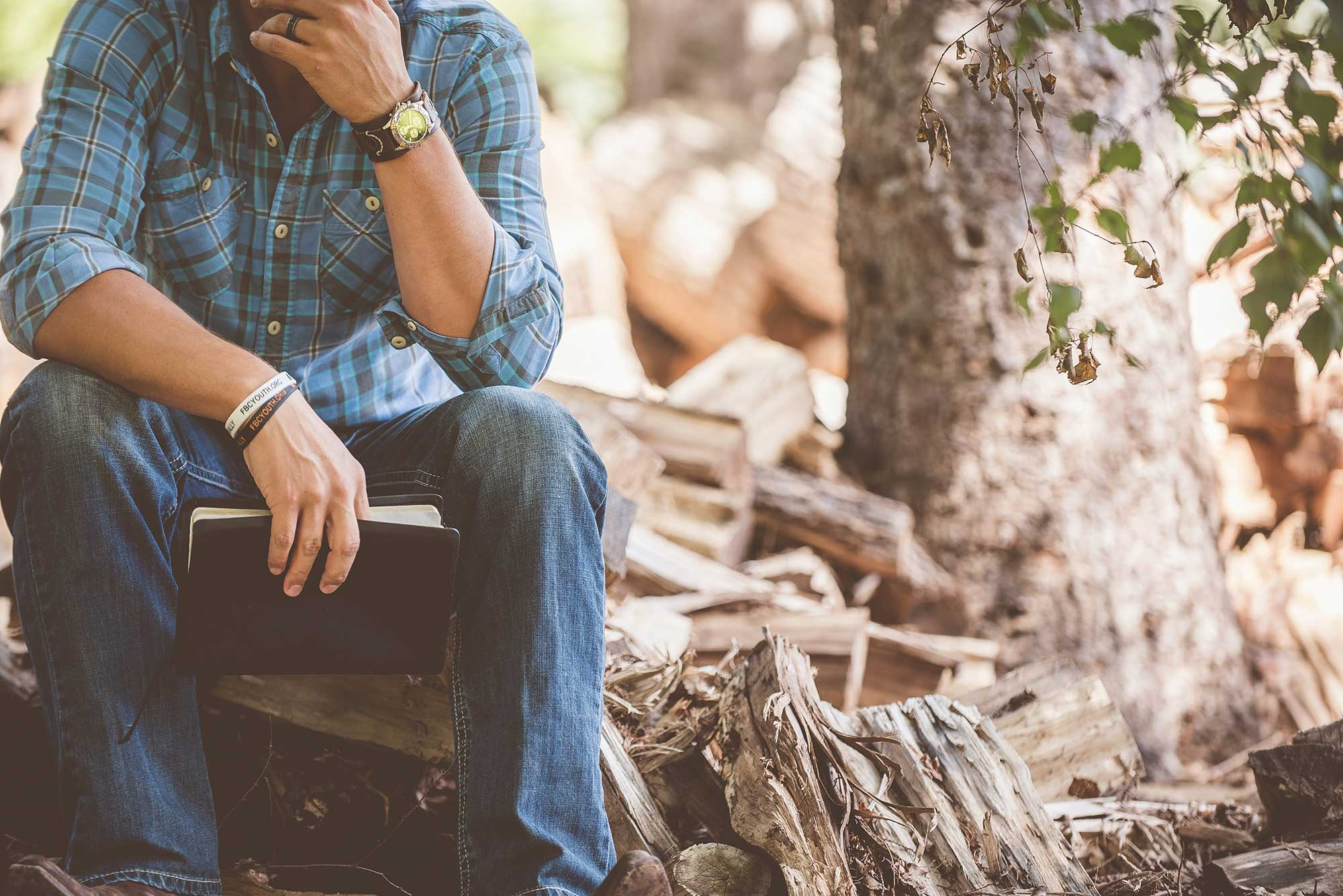 Man sitting on a log with a book in his hands