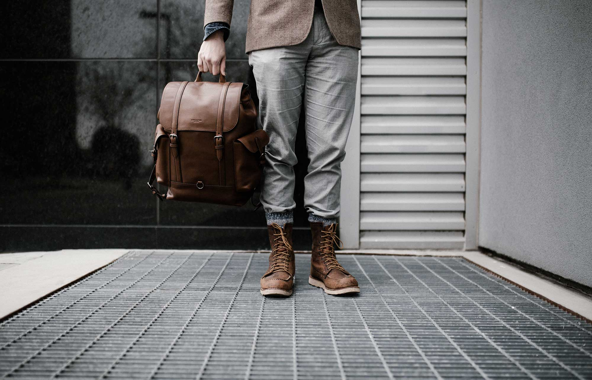 Well-dressed man holding a leather bag