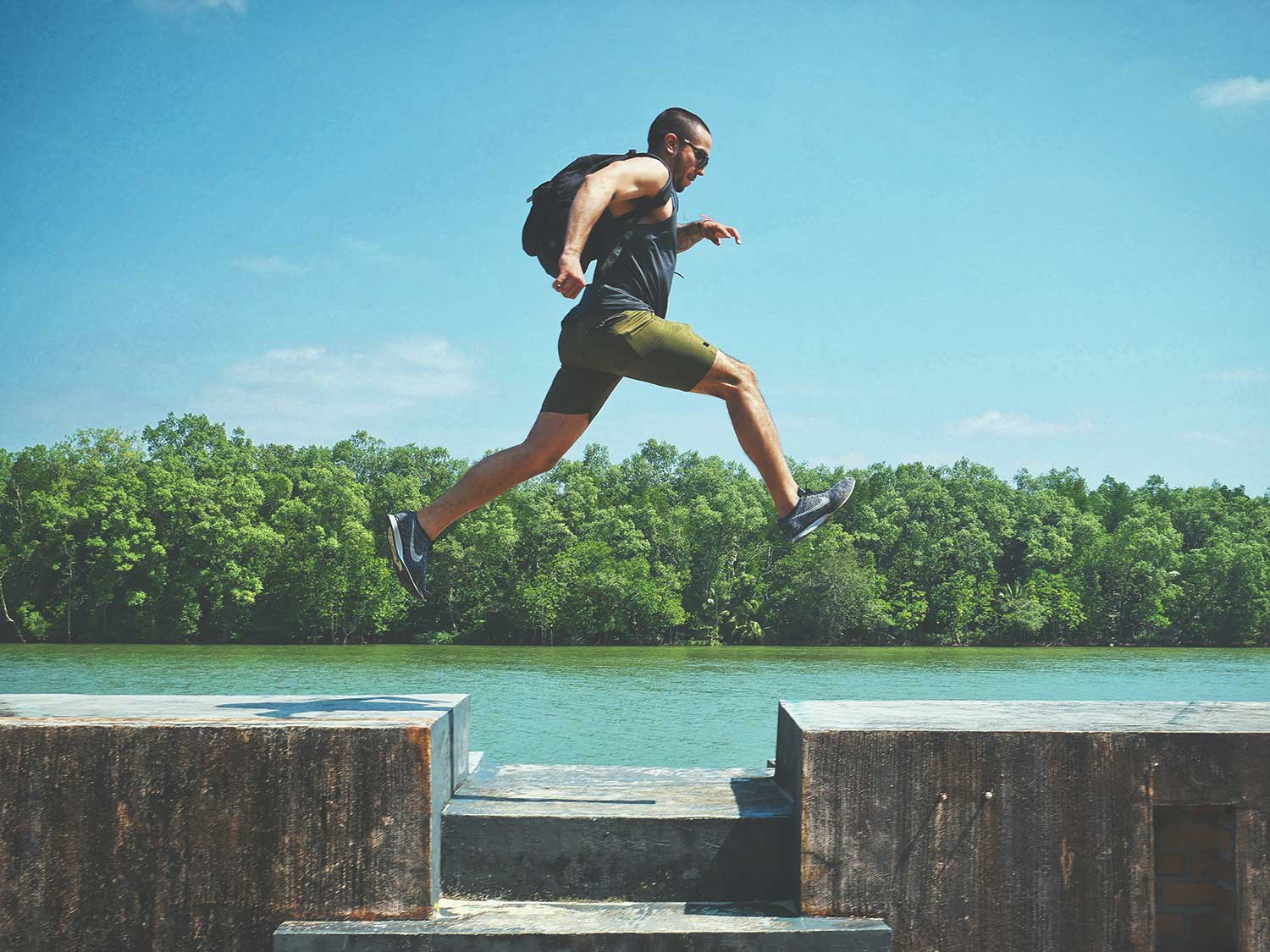 Man jumping over cement wall wearing athletic shorts.