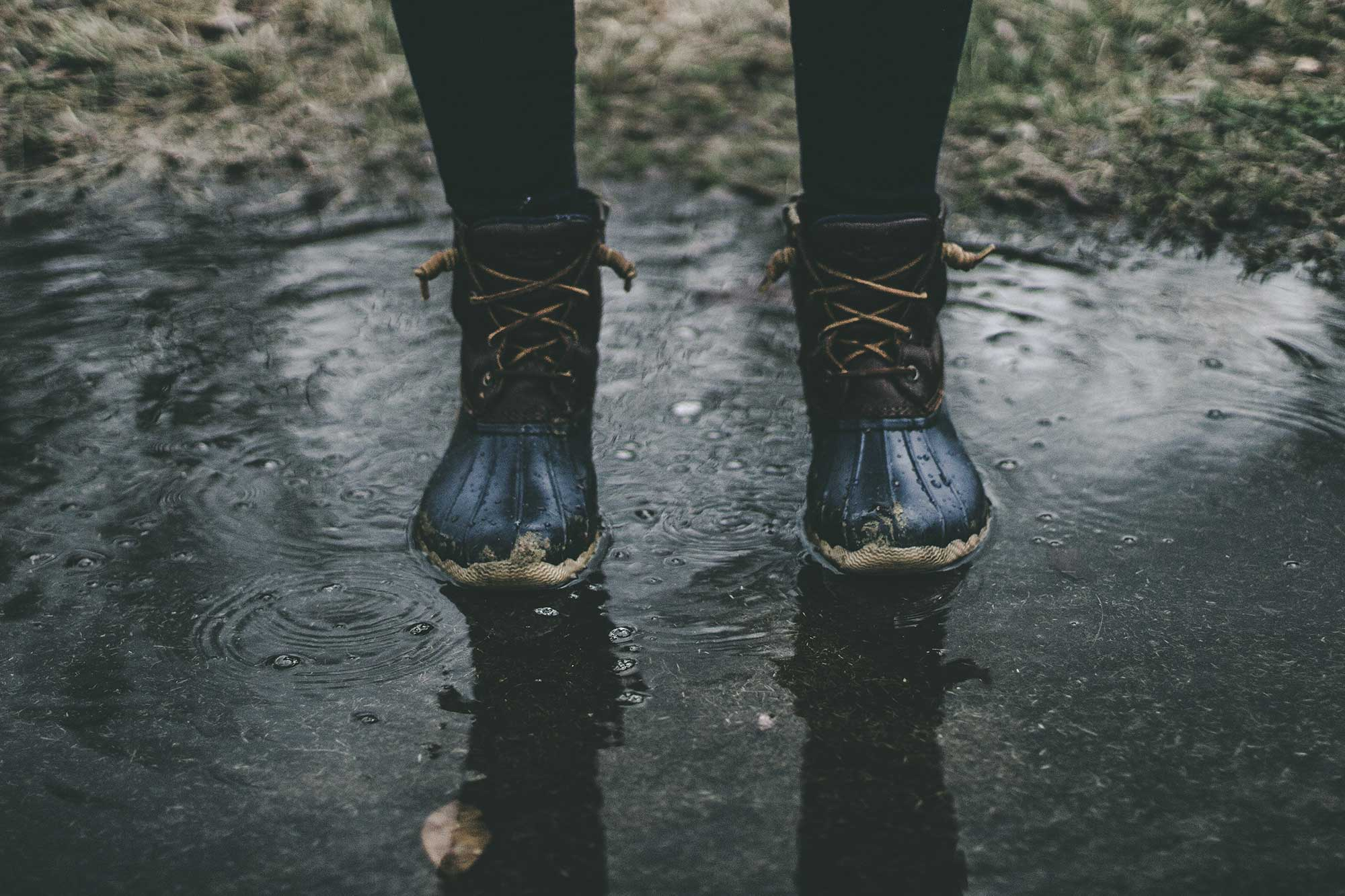 Person standing in a puddle with mudboots on