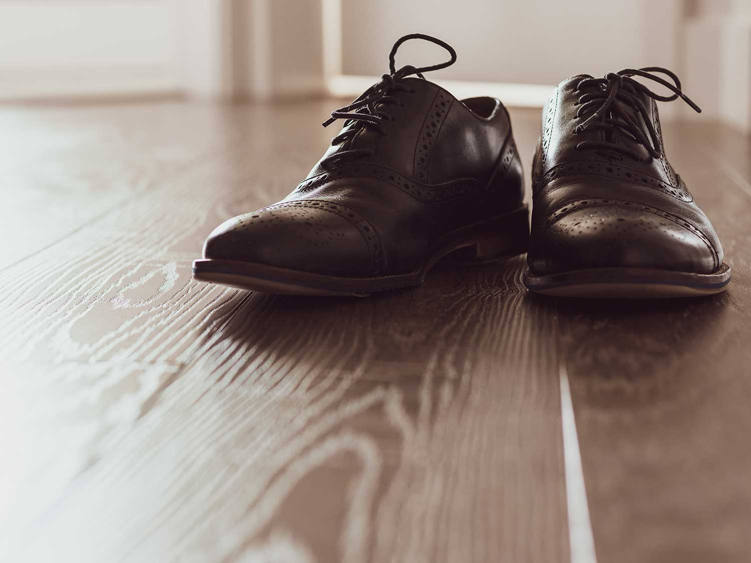 Shined shoes on wooden floor.