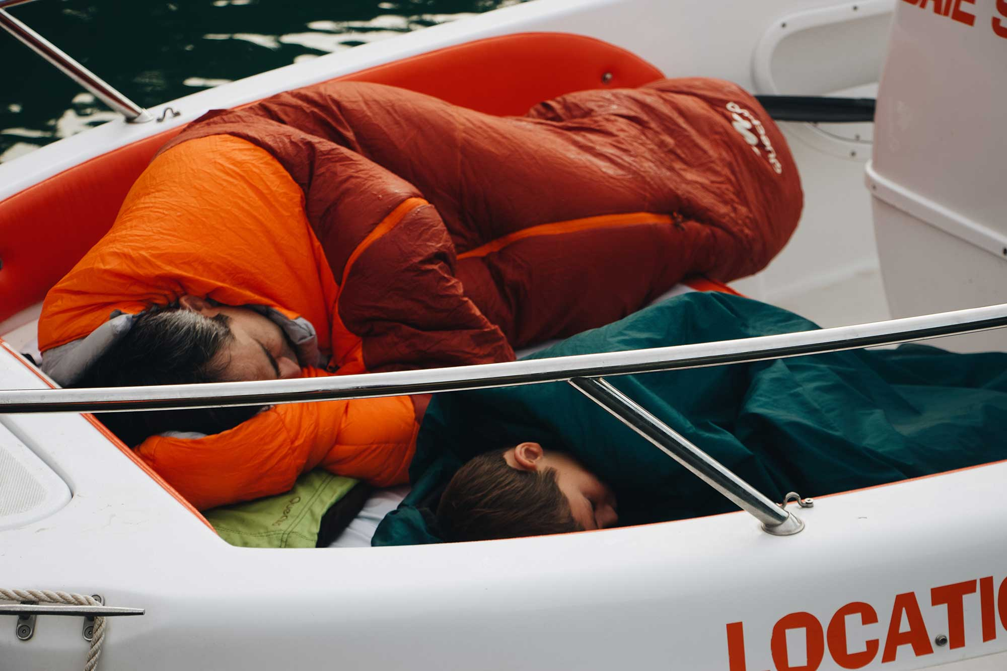 Two people sleeping on a boat