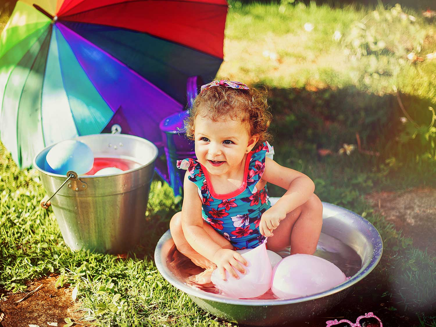 Girl sitting in bucket with water balloons.