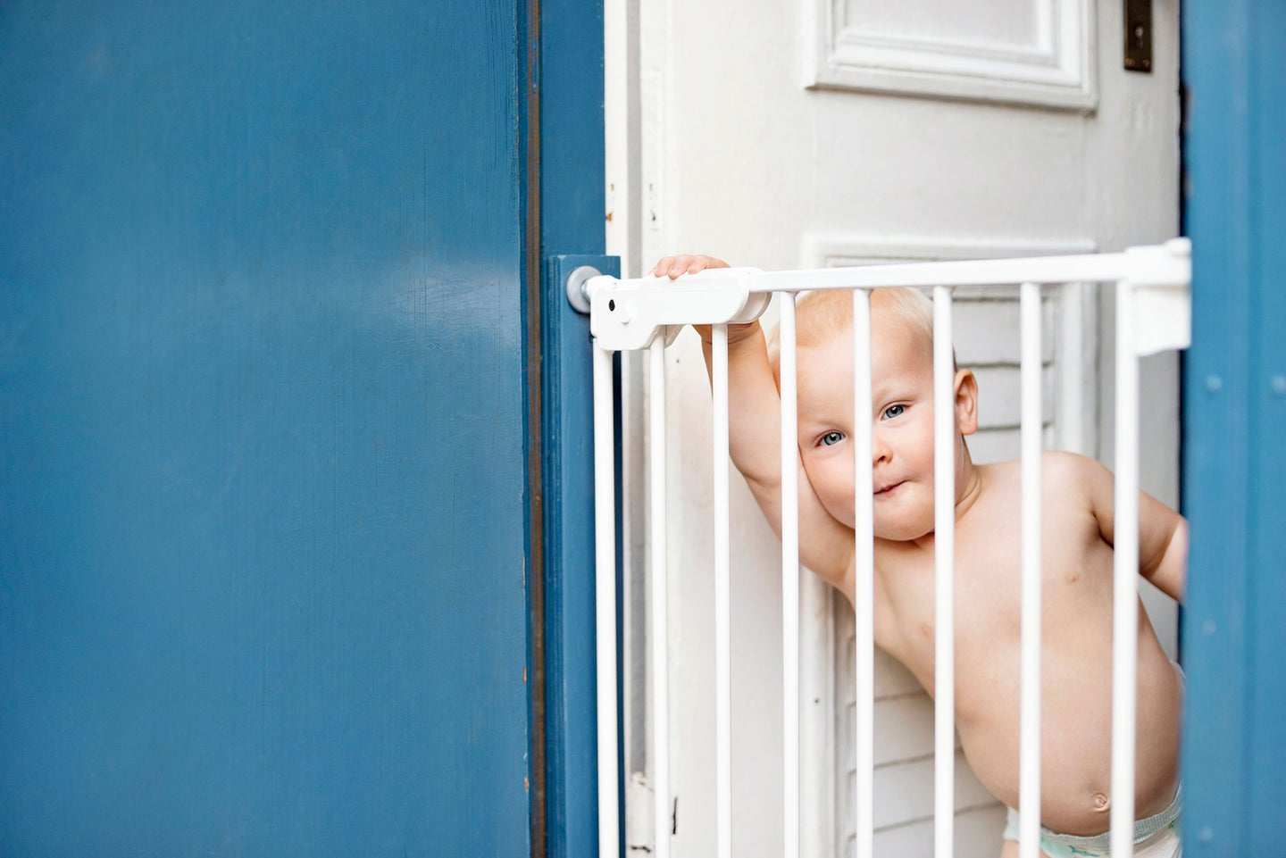 Baby looking out from behind a baby gate