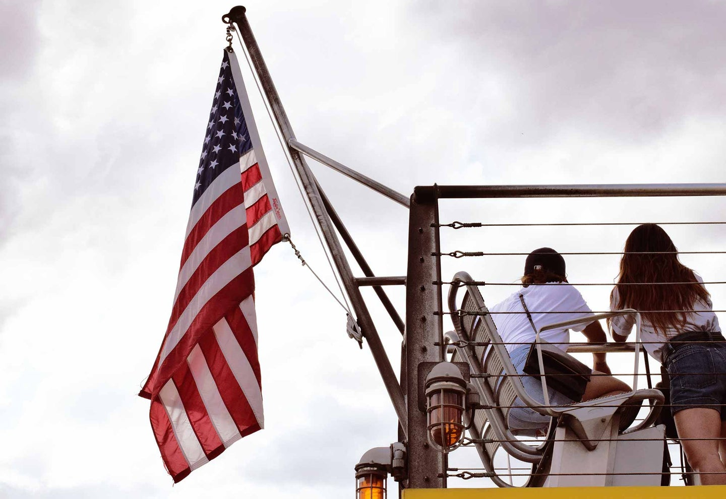 Two people on a balcony beside the American flag