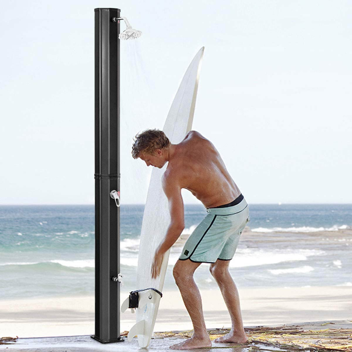Man showering off his surfboard on the beach