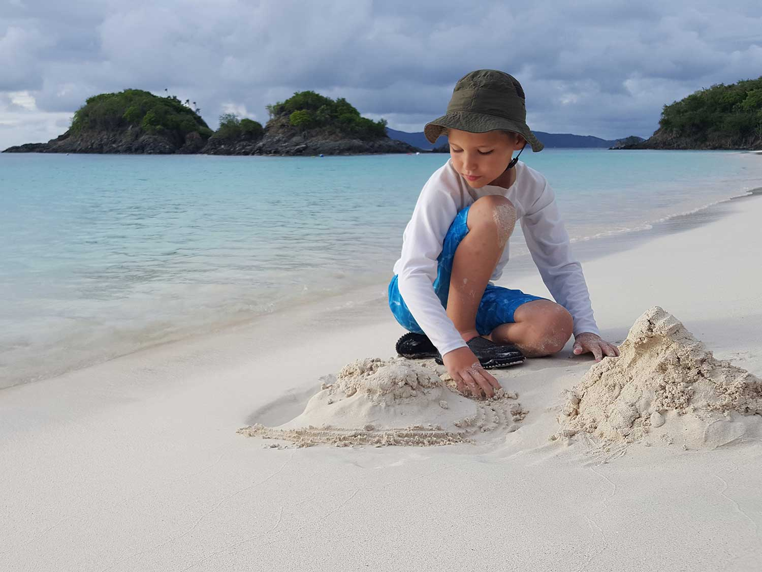 Kid in sand on beach wearing sun hat.