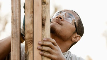 Man working on construction wearing safety goggles.