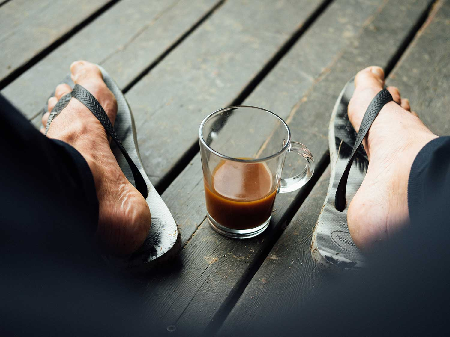 Flip flops on deck with coffee.