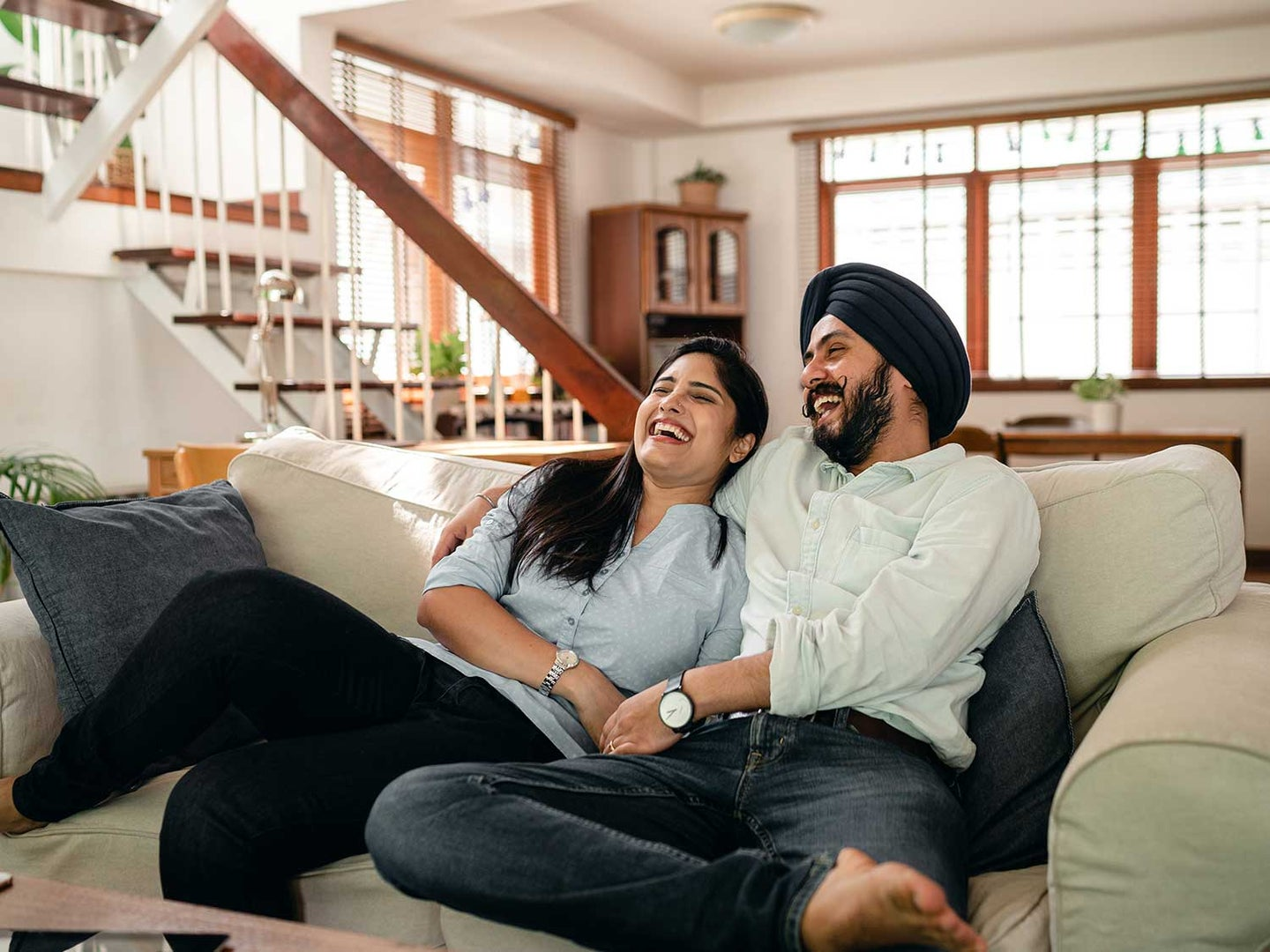Laughing young couple watching movie in at home theater.
