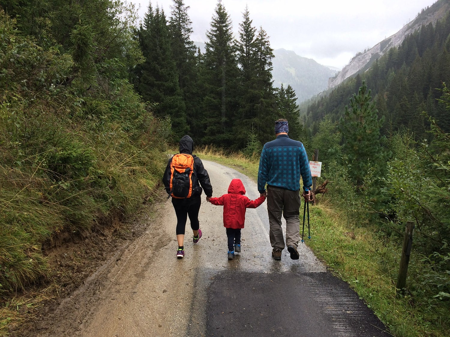 Family walking through on trail in rain surrounded by forest and mountains.