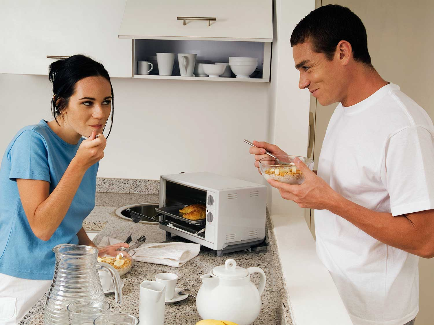Couple eating breakfast by toaster oven in kitchen.