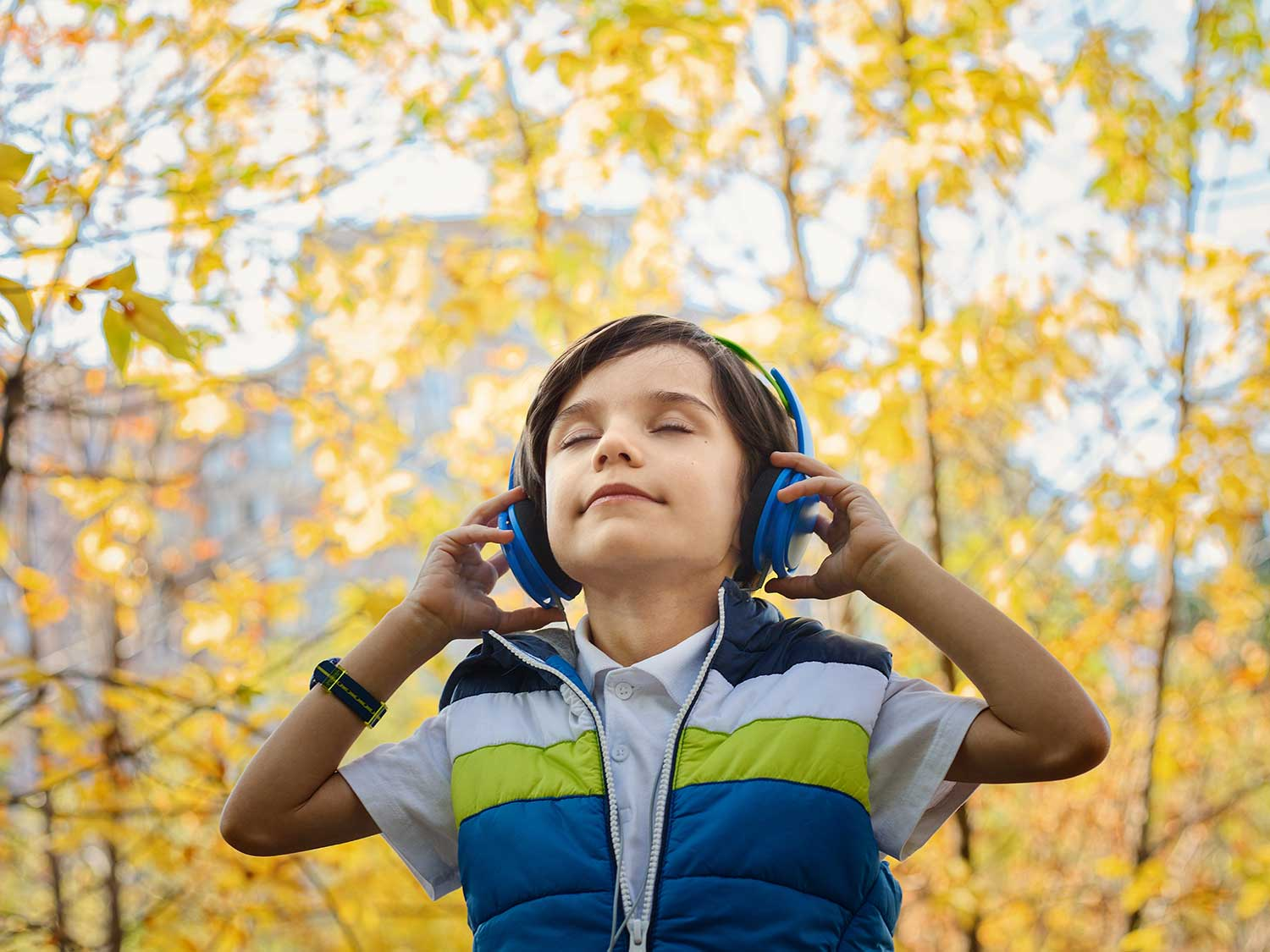 Boy listening to music outdoors with headset.